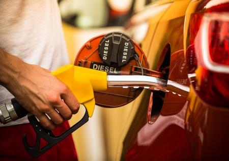 Photo pour Hand refilling the car with fuel, close-up  - image libre de droit