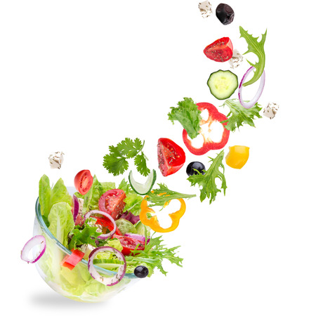 Photo pour Fresh salad with flying vegetables ingredients isolated on a white background. - image libre de droit
