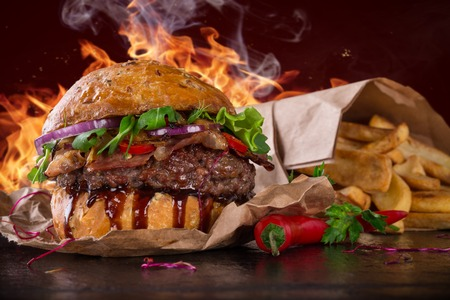 Photo pour Delicious burger with fire flames - image libre de droit