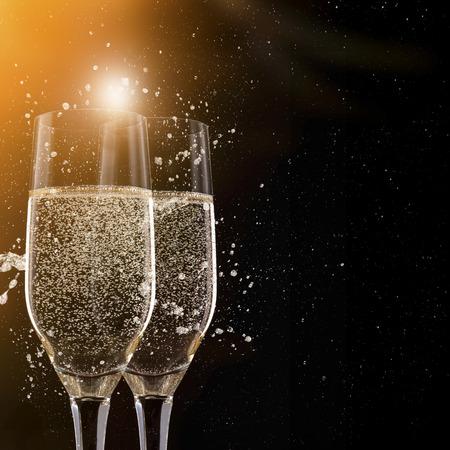 Foto de Champagne flutes on black background, celebration theme. - Imagen libre de derechos