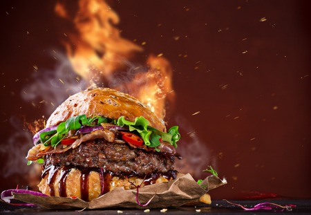 Photo pour Delicious hamburger with fire flames on wooden background - image libre de droit