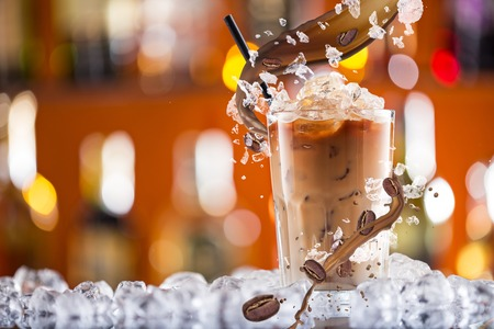 Foto de Cold coffee drink with ice, beans and splash, close-up. - Imagen libre de derechos