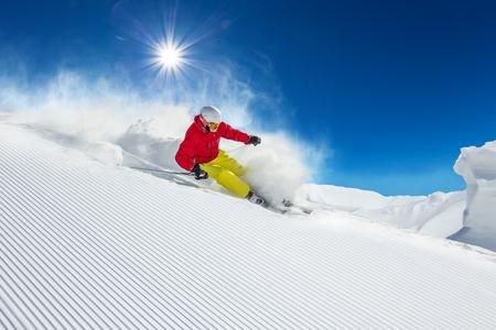 Foto de Skier skiing downhill during sunny day in high mountains - Imagen libre de derechos