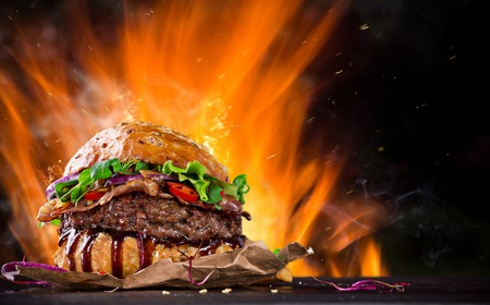 Photo pour Home made Burger with fire flames, close-up. - image libre de droit
