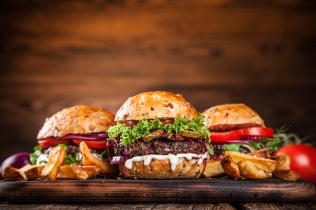 Photo for Close-up of home made burgers on wooden background - Royalty Free Image