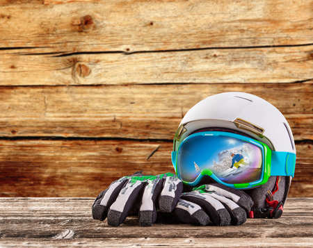 Foto de Colorful ski glasses, gloves and helmet on wooden table. Winter ski theme. - Imagen libre de derechos