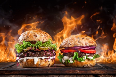 Photo pour Close-up of home made burgers with fire flames. - image libre de droit