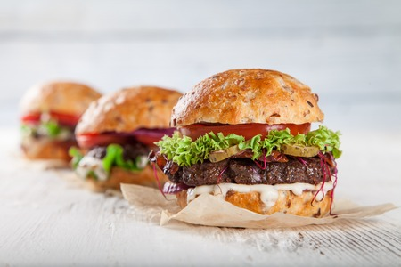 Photo pour Close-up of home made burgers on wooden background - image libre de droit