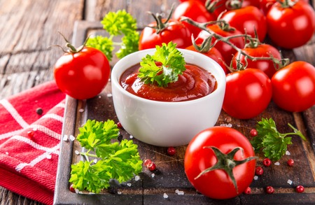 Photo pour Bowl of tomato sauce and cherry tomatoes on wooden table, close-up. - image libre de droit