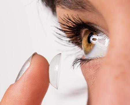 Foto de Young woman putting contact lens in her eye. Macro shot. - Imagen libre de derechos