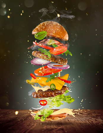 Photo pour Big tasty burger with flying ingredients. - image libre de droit