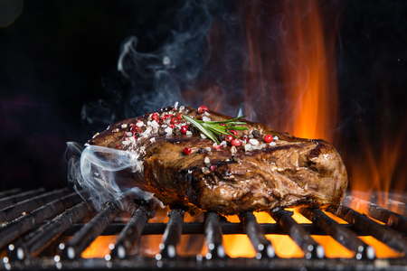 Photo pour Beef steaks on the grill with flames - image libre de droit