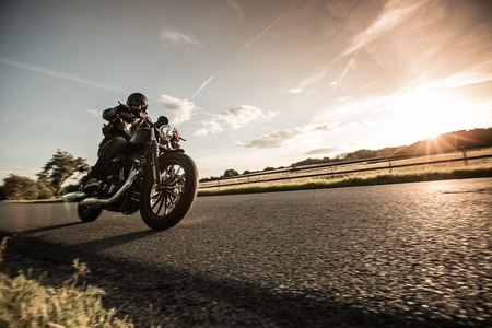 Foto de Man riding sportster motorcycle during sunset. - Imagen libre de derechos