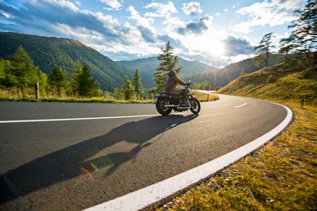 Photo pour Motorcycle driver riding in Alpine highway, Nockalmstrasse, Austria, central Europe. - image libre de droit
