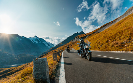 Photo pour Motorcycle driver riding in Alpine highway on famous Hochalpenstrasse, Austria, central Europe. - image libre de droit