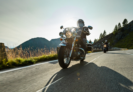 Foto de Motorcycle driver riding japanese high power cruiser in Alpine highway on famous Hochalpenstrasse, Austria, central Europe. - Imagen libre de derechos