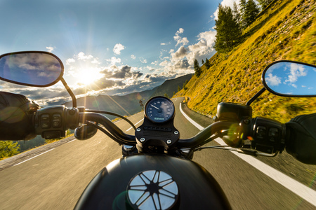 Foto de Motorcycle driver riding in Alpine highway, handlebars view, Austria, central Europe. - Imagen libre de derechos