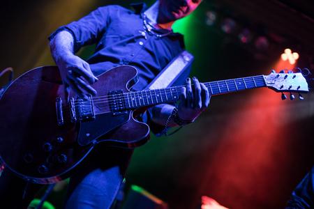 Photo pour Guitarist playing on electric guitar. Rock concert stage. - image libre de droit
