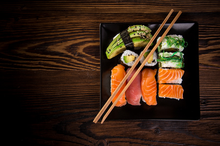 Photo for Various kinds of sushi served on wooden table, top view. - Royalty Free Image