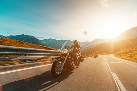 Photo pour Motorcycle driver riding japanese high power cruiser in Alpine highway on famous Hochalpenstrasse, Austria, central Europe. - image libre de droit