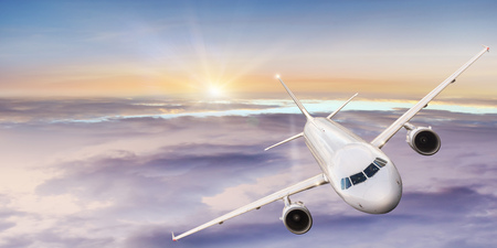 Photo for Commercial airplane flying above dramatic clouds. Wide screen format. - Royalty Free Image