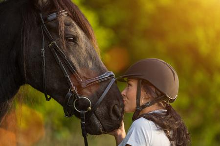 Photo pour Young Woman kissing her horse at sunrise. - image libre de droit
