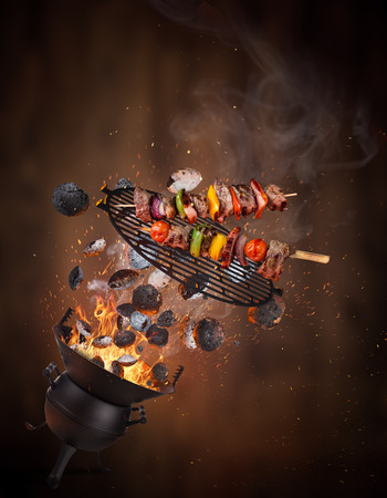 Photo pour Kettle grill with hot briquettes, cast iron grate and tasty skewers flying in the air. Freeze motion barbecue concept. - image libre de droit