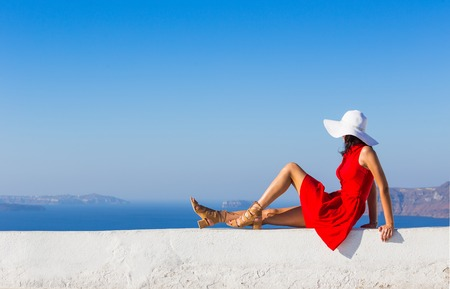 Foto de brunette woman in red dress visiting famous white Oia village. - Imagen libre de derechos