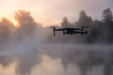 Foto de Drone copter with digital camera, river on background. Modern technology, UAV concept. - Imagen libre de derechos