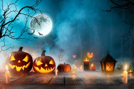 Foto de Halloween pumpkins on dark spooky forest with blue fog in background. - Imagen libre de derechos