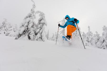 Photo pour Sunny winter landscape with man on snowshoes. - image libre de droit