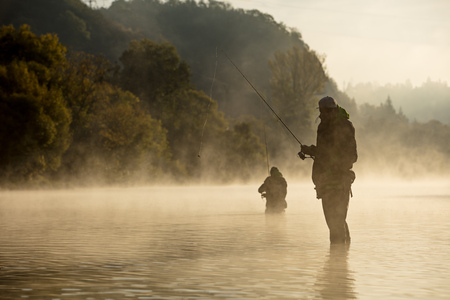 Foto de Men fishing in river with fly rod during summer morning. - Imagen libre de derechos