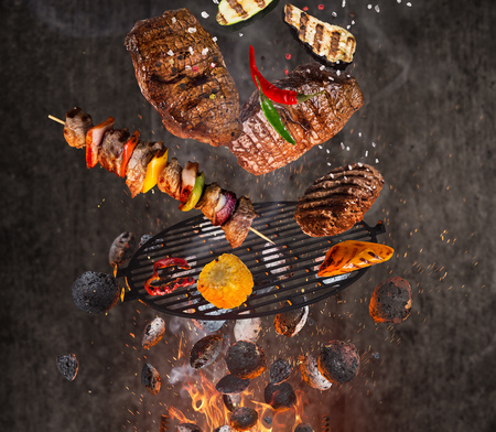 Photo pour Kettle grill with hot briquettes, cast iron grate and tasty meats flying in the air. - image libre de droit