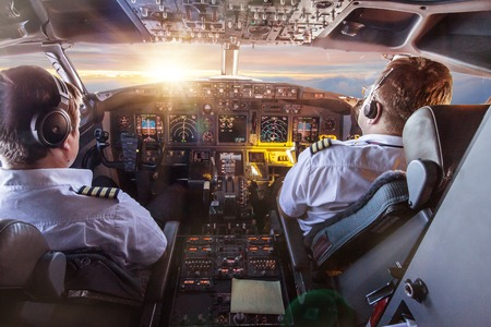 Photo pour Pilots in the cockpit during a flight with commercial airplane. - image libre de droit