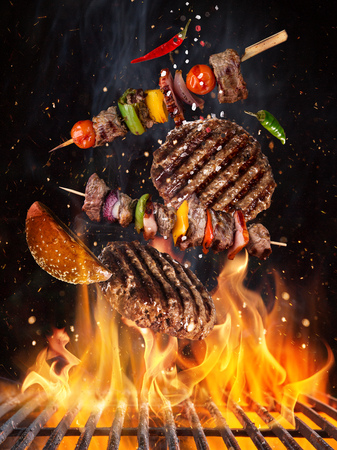 Photo pour Tasty beef steaks and skewers flying above cast iron grate with fire flames. - image libre de droit