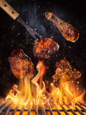 Photo pour Chicken legs and wings on the grill with flames - image libre de droit