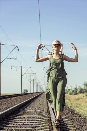 Foto de A young girl of 17 years old blonde with pigtails posing on a railroad bed - Imagen libre de derechos