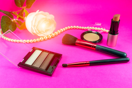 Foto de Brushes and makeup cosmetics are placed on a pink background with pearl necklaces. - Imagen libre de derechos