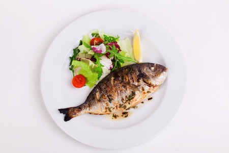 Foto de baked whole fish grilled on a plate with vegetables and lemon on top for the menu - Imagen libre de derechos