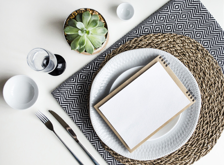 Photo pour Table setting. White dishware, monochrome napkins, Cutlery, glass and plants. The view from the top. - image libre de droit
