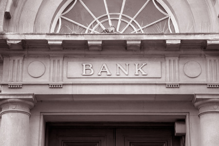 Photo pour Bank Sign over Entrance Door in Black and White Sepia Tone - image libre de droit