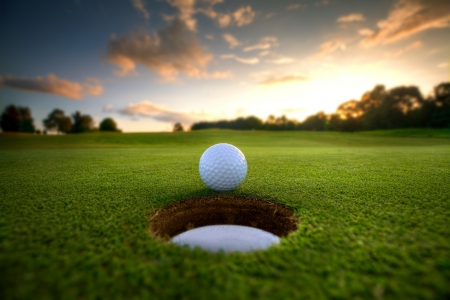 Golf ball about to fall into the cup at sunset