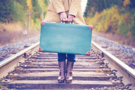 Photo for Elegant woman with a suitcase traveling by rail autumn day. - Royalty Free Image