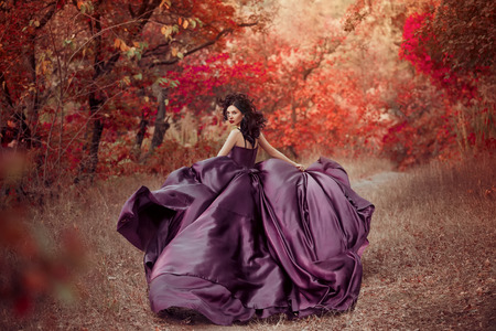 Photo pour Lady in a luxury lush purple dress ,fantastic shot,fairytale princess is walking in the autumn forest,fashionable toning,creative computer colors - image libre de droit