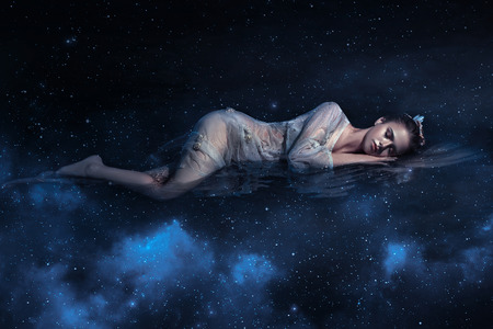 Photo pour Beautiful young girl sleeps in the arms of space among the stars , fantaskicheskaya fotoshoot , fashionable toning , creative color - image libre de droit