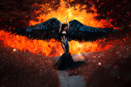 Foto de Black Angel. Pretty girl-demon with black wings. An image for Halloween. Image of an old book of fairy tales. Fashionable toning - Imagen libre de derechos