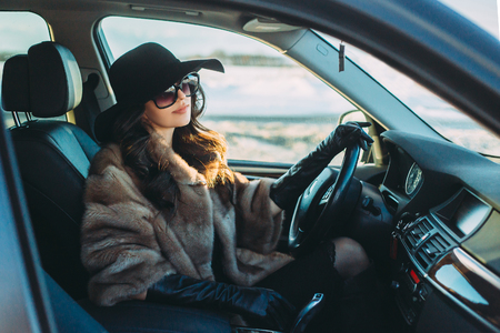 Photo for Young beautiful brunette inside the car with wheel in hands - Royalty Free Image