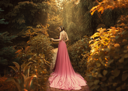 Photo for The Elf walks in the autumn garden. A girl with long ears in a beautiful pink dress with an open back and with a long train. Artistic processing - Royalty Free Image