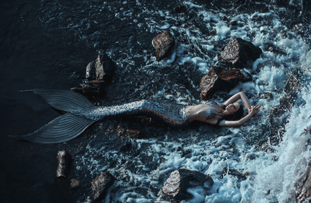 Foto de The real mermaid is resting on the ocean shore. Silver tail, the body is covered with scales. Creative colors - Imagen libre de derechos