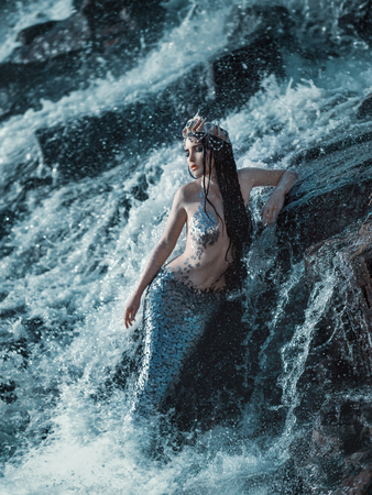 Photo for The real mermaid is resting on the ocean shore. Silver tail, the body is covered with scales. Creative colors - Royalty Free Image